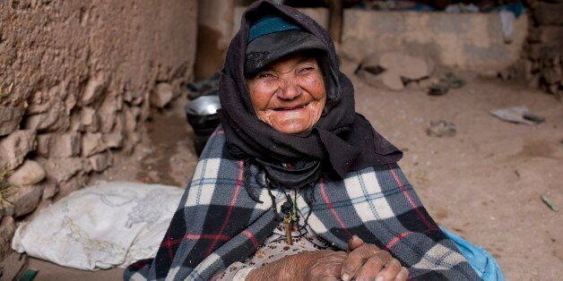 A woman smiles as she warms herself around a fire in her home in Tilmi village in the High Atlas region...