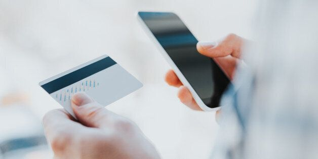 Closeup young man hands holding credit card and using cell, smart phone for online shopping or reporting...