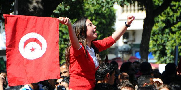 A woman waves a national flag during a demonstration to celebrate Tunisia's independence, Tuesday, March,...