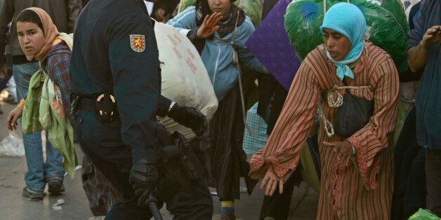 A Spanish policeman hits a Moroccan woman at the border between Spain and Morocco in Ceuta, January 31,...