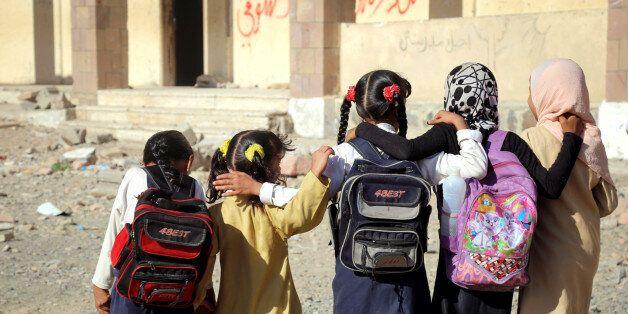 Yemeni school girls walk outside a school on March 16, 2017, that was damaged in an air strike in the...
