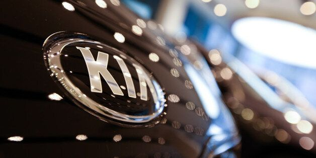 The Kia Motors Corp. logo is displayed on a vehicle in the lobby of the company's headquarters in Seoul,...