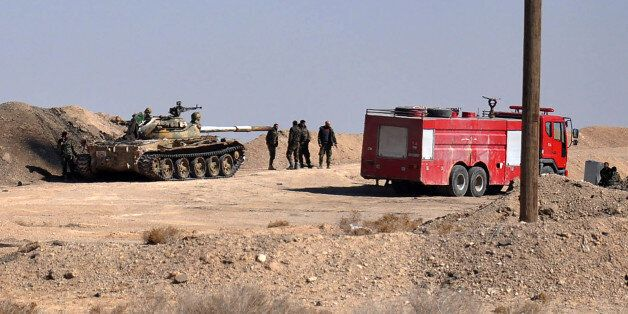 Syrian regime forces gather in a position as they advance towards Hayyan oil field, east of the central...