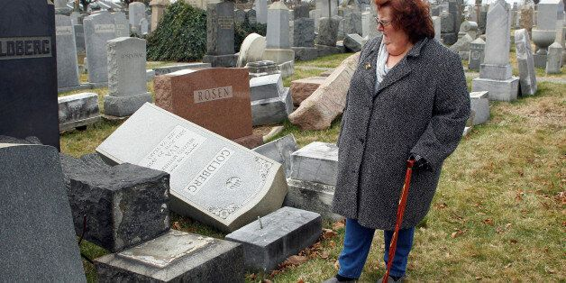 Judy Pogachefsky looks at headstones pushed off their bases by vandals in the Mount Carmel Cemetery,...