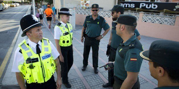 British police officers, popularly known as 'bobbies' walk Spanish Civil Guards as they patrol at Punta...