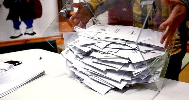 El presidente de una mesa electoral deposita los votos de la urna sobre una mesa para proceder a su