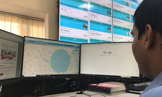An officer looks at computer screens inside a police war room setup to monitor social media posts in...
