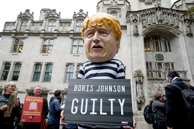A man wearing a giant Boris Johnson mask, dressed as a prisoner, outside the Supreme Court in