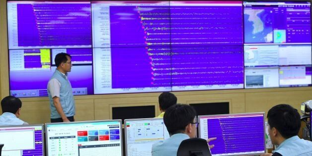 South Korean officials monitor screens showing a graph of seismic waves originating from North Korea,...