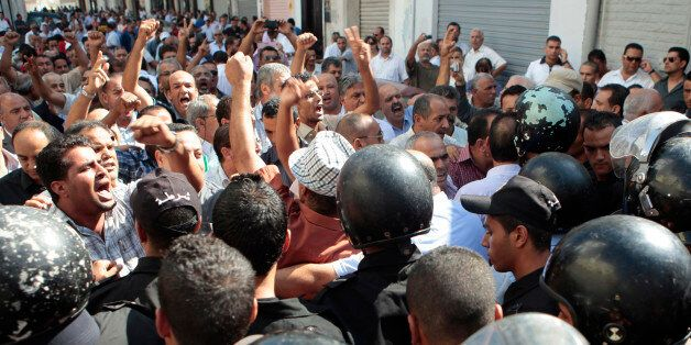 Protesters confront police officers during a demonstration in front of the headquarters of the General...
