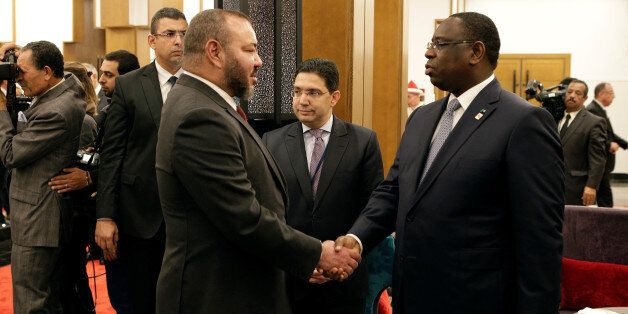 King Mohammed VI of Morocco (L) shakes hand with President of Senegal Macky Sall at the opening of the...
