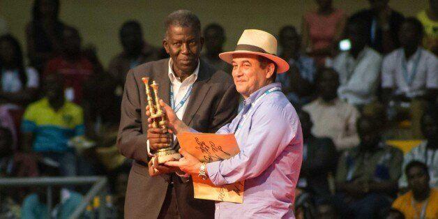 OUAGADOUGOU, BURKINA FASO - MARCH 05: Algerian film director Lotfi Bouchouchi (R) holds the award after...