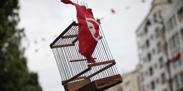 TUNIS, TUNISIA – JANUARY 14: An empty cage of bird decorated with a Tunisian flag is seen raised during...