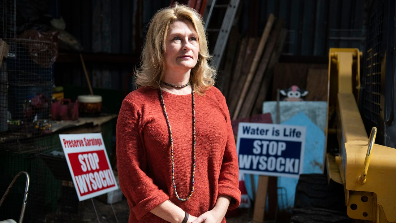 Rhonda Carrell shows signs promoting Protect Wood County's message to protect against Wysocki Family of Companies, mega-dairies and farms near her home in Saratoga, Wisconsin, on Sept. 20. Photo by Lauren Justice