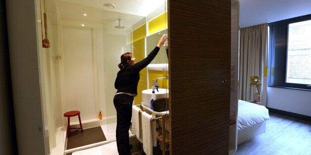A chambermaid cleans the bathroom of a room at the Qbic Hotel London City, operated by Qbic Hotels, in...