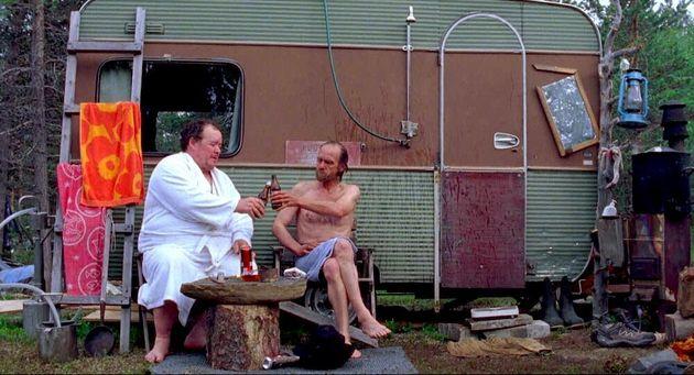 自分の過去を語った後、サウナの外でビールを楽しむ男性たち