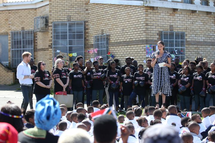 Harry looks on as Meghan speaks during the Justice Desk initiative in Nyanga township, on the first day of their African tour