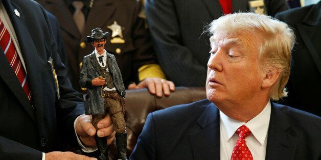 U.S. President Donald Trump receives a figurine of a sheriff during a meeting with county sheriffs at...