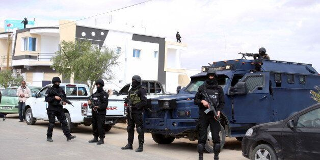 Tunisian police officers stand guard near a cemetery where soldiers and civilians who were killed during...