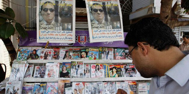 A man reads the headlines of local newspapers in Cairo June 3, 2012, a day after former leader Hosni...