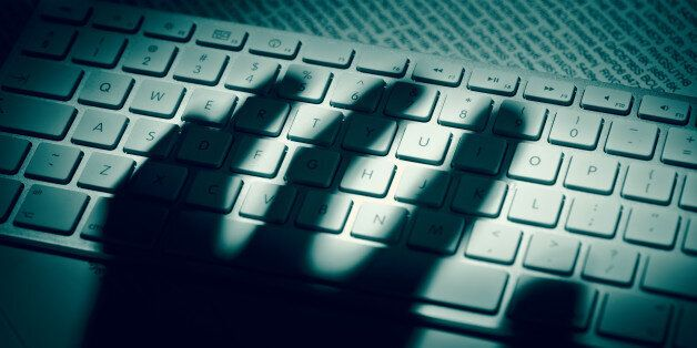A menacing hand'€™s shadow on a computer keyboard in front of printed computer data. Dramatic light,...