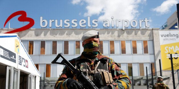 A Belgian soldier stands guard outside the partially reopened departure hall of Zaventem international...