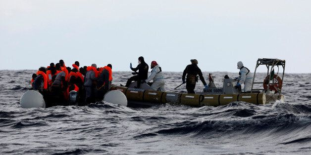 Italian Navy personnel rescues migrants from their overcrowded raft, as lifeguards from the Spanish NGO...
