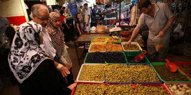 People shop at Ali Mellah market in Algiers on July 27, 2011. Faced with crumbling regimes across the...