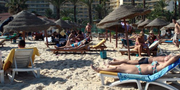 Tourists enjoy the beach near a four-star hotel in the resort town of Sousse, a popular tourist destination...
