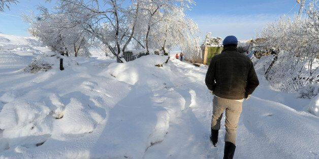 A man walks on a road covered with snow in the village of Medea, 100km south of Algiers, on February...