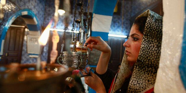 A Jewish worshipper lights an oil lamp during a pilgrimage to the El Ghriba synagogue in Djerba April...