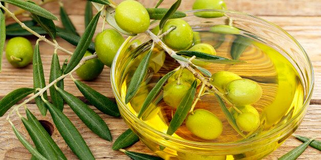 olive tree branch dipped in bowl of olive