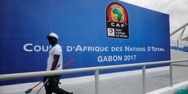 A worker walks past a billboard at the Stade de l'Amitie Sino ahead of the African Nations Cup Soccer...