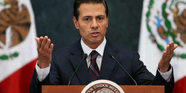 Mexico's President Enrique Pena Nieto gestures as he addresses to the media to announce new cabinet members...