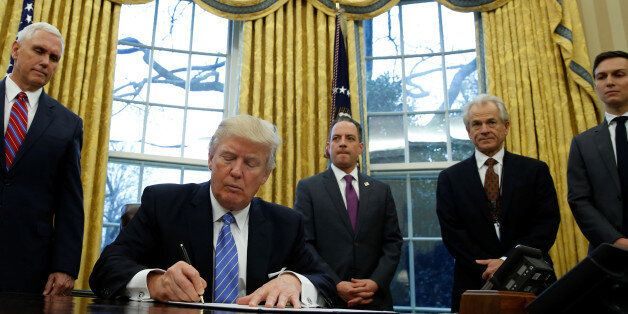 U.S. President Donald Trump, watched by (L-R) Vice President Mike Pence, White House Chief of Staff Reince...