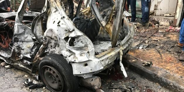 A general view shows a burnt-out vehicle at the site of a car bomb explosion in Syria's coastal city...