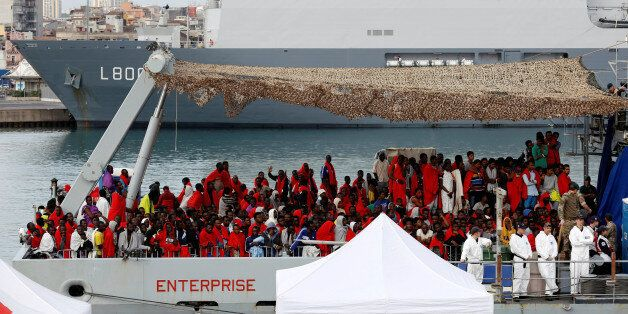 Migrants wait for disembark from Royal Navy Ship HMS Enterprise in the Sicilian harbour of Catania, Italy,...