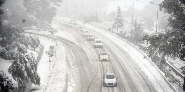 Cars drive on snow on February 4, 2012 on a highway on the outskirts of Algiers after a snowfall. AFP...