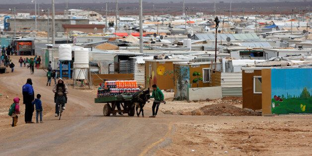 Syrian refugees are seen during rainy weather at the Al Zaatari refugee camp in the Jordanian city of...