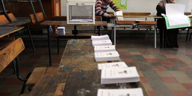 Algerian election commission officials wait for voters in a classroom turned into a polling station in...