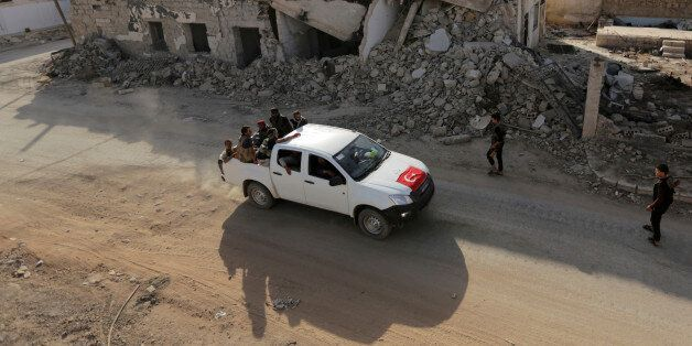 Free Syrian Army fighters ride on a pick-up truck decorated with a Turkish flag past damaged buildings...