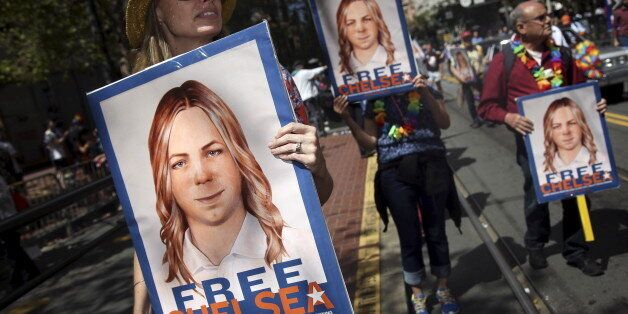 People hold signs calling for the release of imprisoned wikileaks whistleblower Chelsea Manning while...