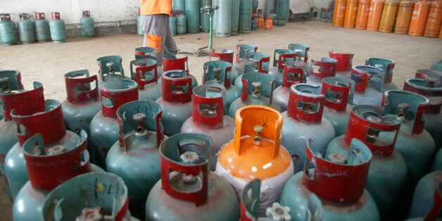 A worker carries a cylinder of Liquefied Petroleum Gas (LPG) in Foshan, Guangdong province, October 20,...