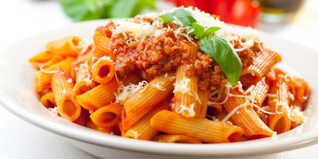 Plate of penne bolognese with ingredients in the