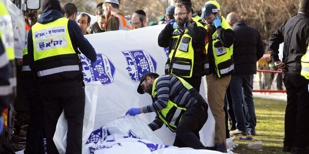 EDITORS NOTE: Graphic content / Israeli security forces and emergency personnel gather at the site of...