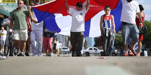MIAMI, FL - NOVEMBER 26: People hold a Cuban flag in the streets as they react to the news of the death...