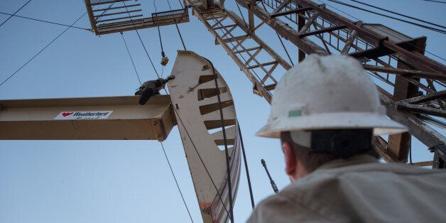 Oil field workers with Wisco work on pump jack in Tioga, N.D., Nov 6, 2013. Back in 2008 the North Dakota...