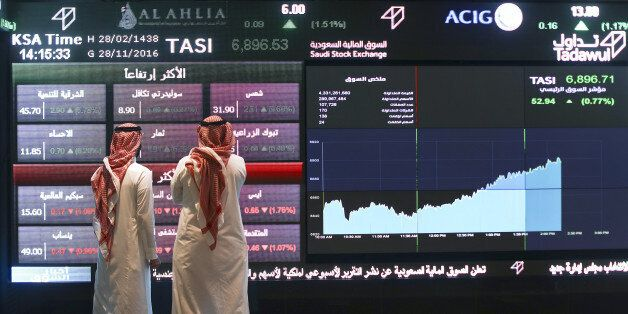 Visitors stand and watch stock movements displayed on large video screens inside the Saudi Stock Exchange,...