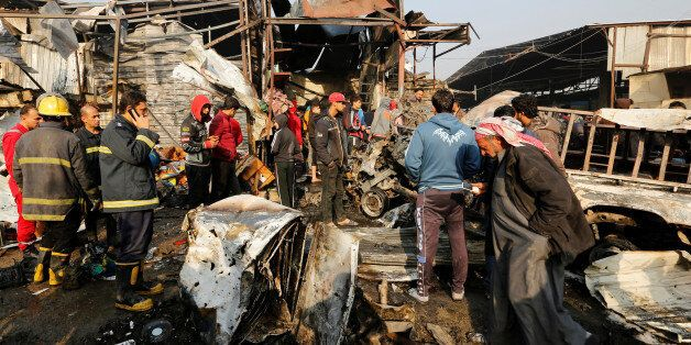 Firemen and people gather at the site of a car bomb attack at a vegetable market in eastern Baghdad,...