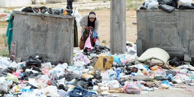 GO WITH STORY BY MARINE MESSINA - A woman inspects uncollected rubbish poured on the ground on May 27,...